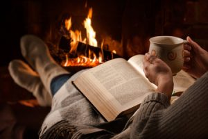 54094138 - woman resting with cup of hot drink and book near fireplace copyright Alexander Raths
