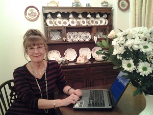Author K.L Loveley typing at her laptop